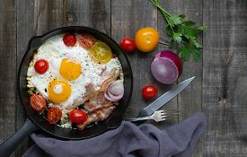 Cast Iron Frying Pan With Eggs, Bacon And Tomatoes On Wooden Background. Top View, Flat Lay.
