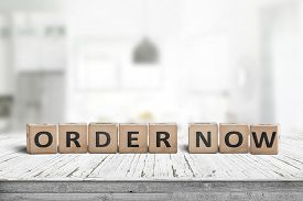 Order Now Sign On A Wooden Table In A Brigh Living Room With Interiors