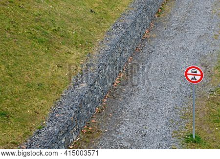 A Gabion Retaining Wall Holds An Anti-erosion Slope Above The Dirt Gravel Path For Bicycles And Hike