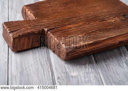 Handcraft Dark Brown Teak Wooden Old Cutting Board, Grey Background, Angle View Selective Focus