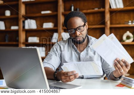 Serious Black Man With Black Square Glasses, Concentrated Reading From Whom Letters, Received A Bad
