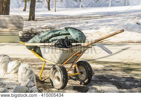 Metal Garden Wheelbarrow With Gardener's Tools: Shovel, Rake, Work Clothes. Spring Gardening Work In