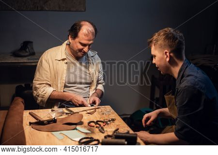 An Elderly Shoemaker And His Apprentice Create Shoes By Hand In Their Workshop With Various Tools.