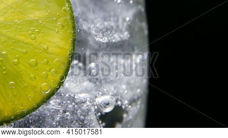 Macro Close-up, Refreshing Soda Tonic Fizzy Water, Lime In Glass, Ice. Slice Of Lemon, Mineral Bubbl