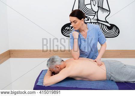 Pretty, Brunette Masseuse Doing Back Massage To Mature Man.