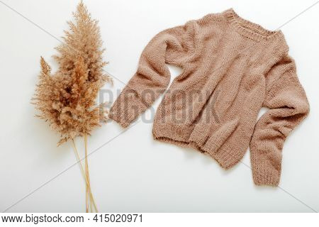 Knitted Soft Beige Sweater On Hanger With Reed Branch. Warm Stylish Homewear Winter Spring Outfit Br