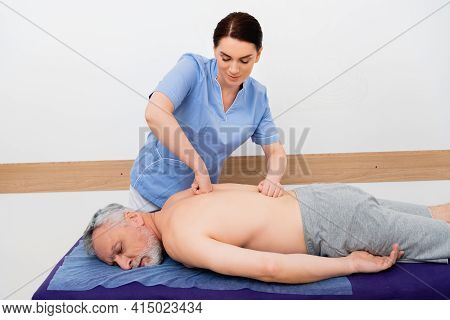 Pretty, Brunette Masseuse Doing Back Massage To Mature Man In Hospital.