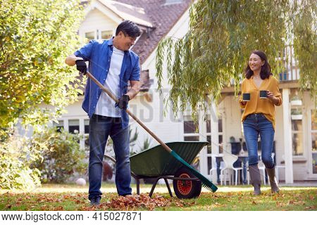 Mature Asian Woman Bringing Hot Drink To Man Tidying Garden With Rake