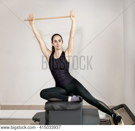 A Woman Doing Pilates Exercises With A Wooden Stick On A Reformer Bed.