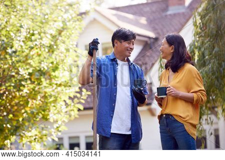 Mature Asian Couple Taking A Break With Hot Drinks Whilst Tidying Garden With Rake