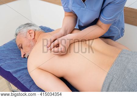 Masseuse Doing Back Massage To Mature Man Lying On Massage Table.