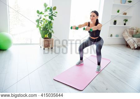 Full Body Photo Of Pretty Skinny Person Hands Hold Dumbbells Squatting On Pink Fitness Carpet Indoor