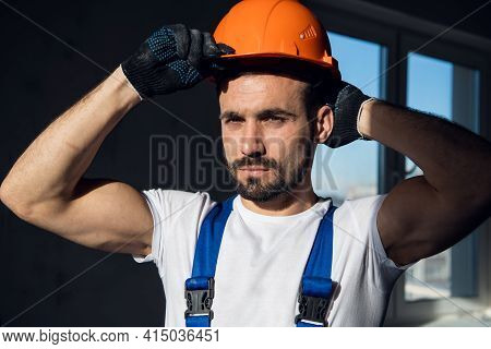 Workman In Blue Overalls Holds On To The Visor Of A Hard Hat