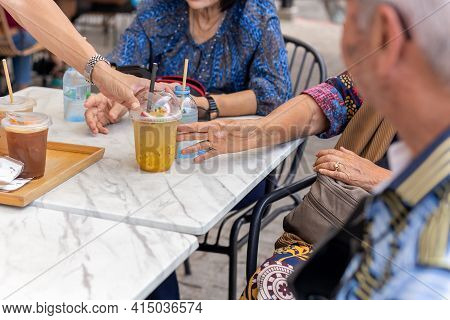 Waiter Serving Glass Of Fresh Juice To Elderly People On Table.