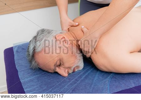 Masseuse Doing Neck Massage To Mature Man In Rehabilitation Center.