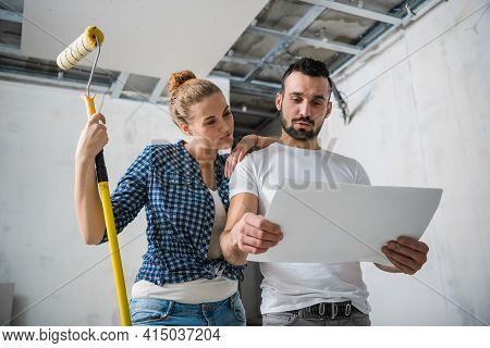 Married Couple Holding Apartment Plan In Hands And Smiling