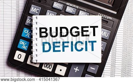 On The Table Are Reports, A Calculator And A Card With The Words Budget Deficit On It. Business Conc
