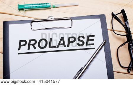 The Word Prolapse Is Written On A White Piece Of Paper Next To Black-rimmed Glasses, A Pen And A Syr