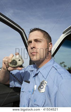 Portrait of male paramedic communicating on walkie-talkie