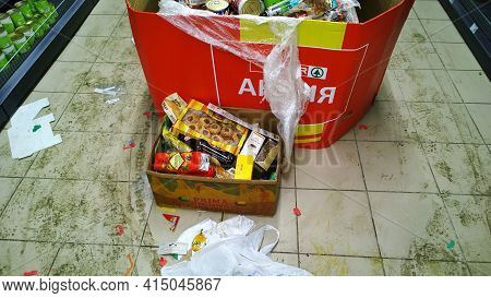 St. Petersburg, Russia - December, 2019: Cardboard Box With Food On Dirty Floor. Clutter And Scatter