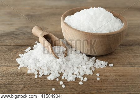 Natural Sea Salt, Bowl And Scoop On Wooden Table