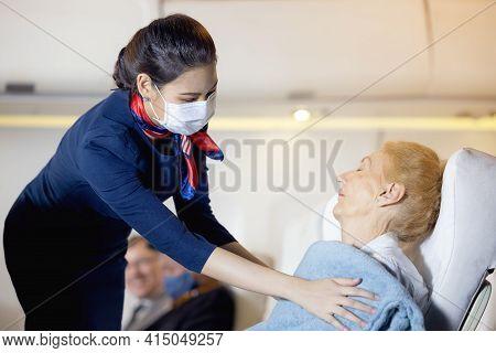 A Female Flight Attendant Clothed An Elderly Passenger Sleeping In The Passenger Seat. Stewardess Ta