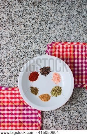 Ensemble Of Spices In A White Dish Over A Granite Countertop. Top Down View.