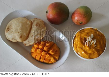 Deep Fried Indian Flat Bread Served With Mango Pulp Locally Known As Aamras. Mango Pulp Is Made From