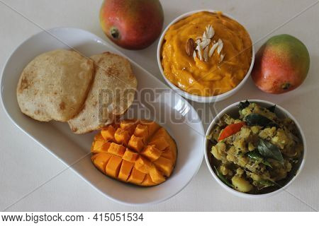 Puri Served With Mango Pulp And Potato Masala. Locally Known As Puri Masala And Aamras. Popular Nort