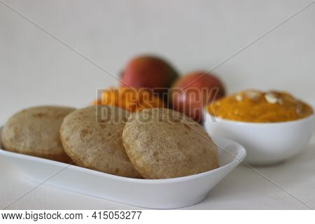 Puri Served With Mango Pulp Locally Known As Aamras. Mango Pulp Is Made From Lalbagh Mango. A Sweet