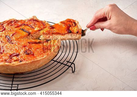 Womans Hand Holds On A Shoulder Blade Piece Of Homemade Quiche Pie With Chicken, Dried Tomatoes, Che