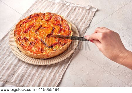 Womans Hand Cuts With A Knife Homemade Quiche Pie With Chicken, Dried Tomatoes, Cheddar Cheese On Ce