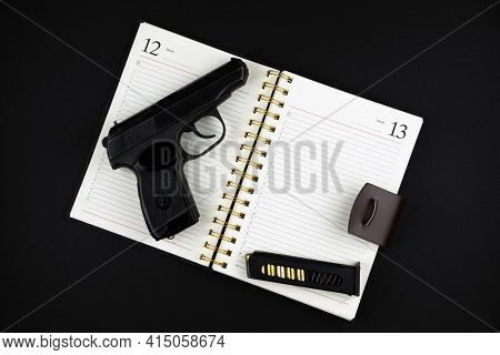 A Traumatic Pistol And Ammunition Are Lying On An Open Notebook On A Black Background