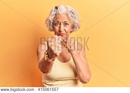 Senior grey-haired woman wearing casual clothes punching fist to fight, aggressive and angry attack, threat and violence