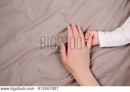 Top View Close Up Of Unrecognizable Gentle Caring Mom Holding Tender Baby Hand Lying Together On Bed