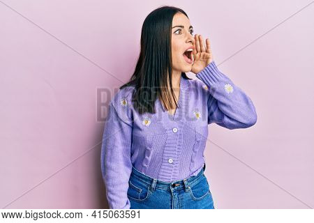 Young brunette woman wearing spring cardigan with flowers print shouting and screaming loud to side with hand on mouth. communication concept.