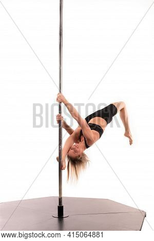 Slim Girl Performing Acrobatic Exercise On Pole