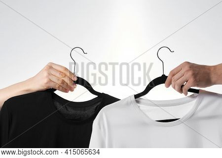 Basic Wear. Hand Holding Black T-shirt On A Hanger Against White Background. Casual Clothes For Men,