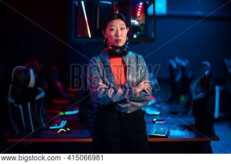 Young Asian Gamer In A Headset Poses For The Camera With Her Arms Folded