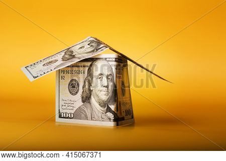 House Made From 100 Dollar Bills Cash Money On Yellow Background.