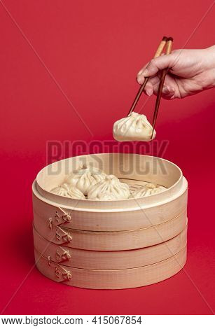 Woman Taking A Dumpling From The Bamboo Steamer With The Chopsticks. Freshly Steamed Baozi Dumplings