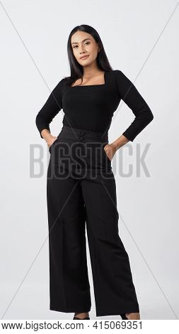 Young Woman Posing In Black Shirt And Pants In The Studio On White Background.