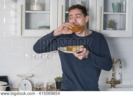 Portrait Of Hungry Guy, Young Man In Pyjama Is Eating Tasty Sandwich, Biting Burgers At Home At Kitc