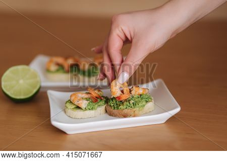 Female Hand Put Shrimps On Bruschetta Toast With Avocado. Healthy Appetizer Of Bruschetta With Guaca