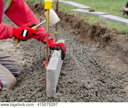 Laing Edging Kerb On Semidry Concrete During Roadworks And New Footpath Construction  By Groundworke