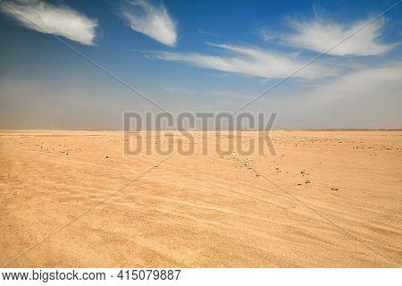Dry Desert Landscape. Hot Lifeless Sand Of Desert And Blue Sky In Summer Sunny Day. Flat Desert Of E