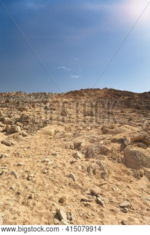 Hillside With Rocks In Dry Desert. Egypt Hot Lifeless Sand And Rock Mountain And Blue Sky In Summer