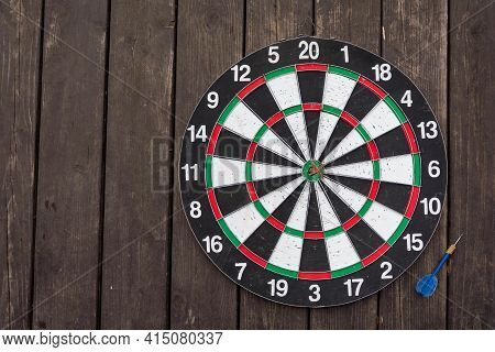 Dart Board On Dark Wood Background With Copy Space. A Dart In The Bull's-eye. Achieving The Goal. Su