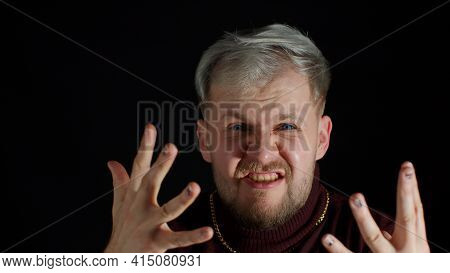 Portrait Of Angry Annoyed Young Man Screaming To The Camera With Raised Hand Against Black Backgroun