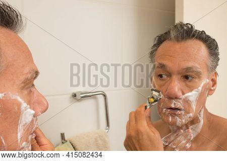 Senior Man In The Bathroom With Shaving Cream On His Face Shaving